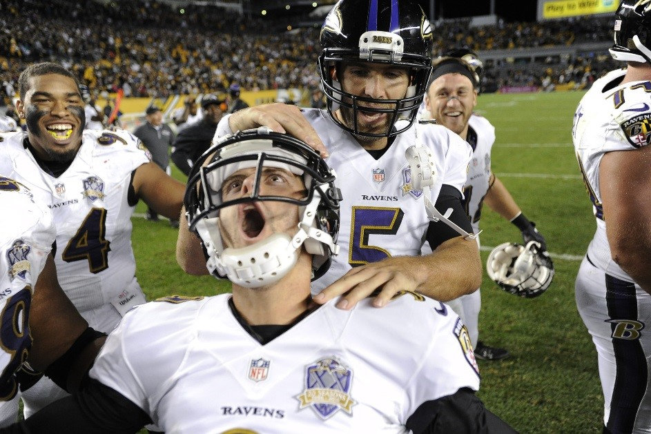 "Justin Tucker screaming ""woo!"" as Joe Flacco pats him on the helmet. Both wearing their white jerseys at Heinz Field in Pittsburgh"