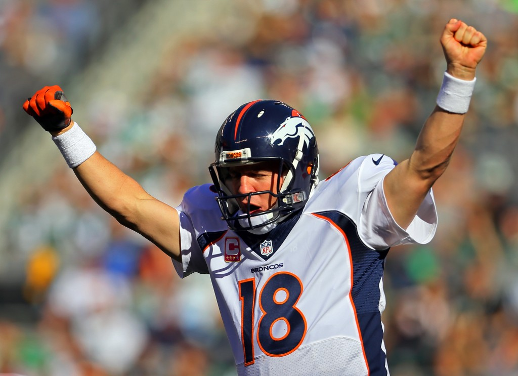 Broncos QB Peyton Manning raises both arms in the air while making checks at the line of scrimmage.
