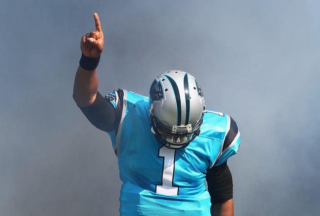 Panthers QB Cam Newton raises one finger in the air, signaling to the crowd as he walks out of the tunnel.