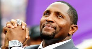 Ray Lewis with his hands held like he's saying a prayer in a suit.