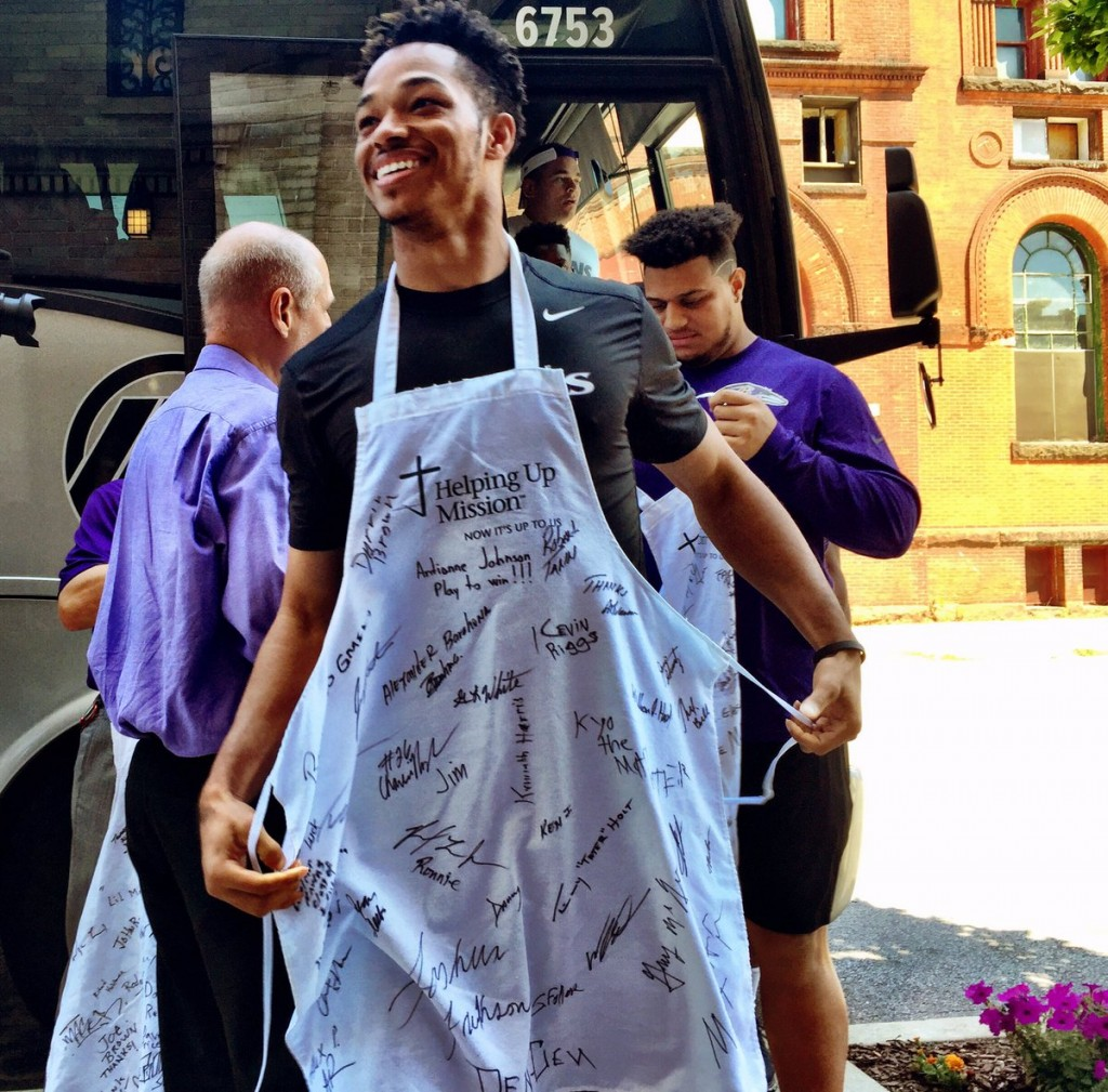 Ravens rookie WR Chris Moore wearing an apron outside of Helping Up Mission.