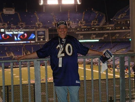 A man in an Ed Reed jersey stands on the concourse at M&T Bank Stadium, the seating bowl behind him.