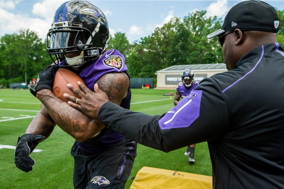 Ravens RB Coach Thomas Hammock teaches the running backs how to carry the football using the HnTv1 ball.