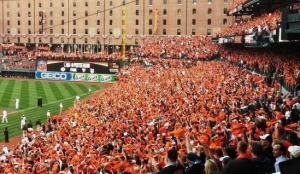 Loud Orioles fans at Oriole Park at Camden Yards (OPACY) waving orange towels and filling the stands.