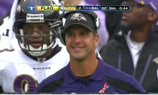 John Harbaugh smiles on the TV broadcast.