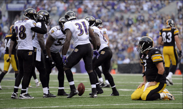Ravens players huddle around a spinning football while Ben Roethlisberger looks on from his knees.