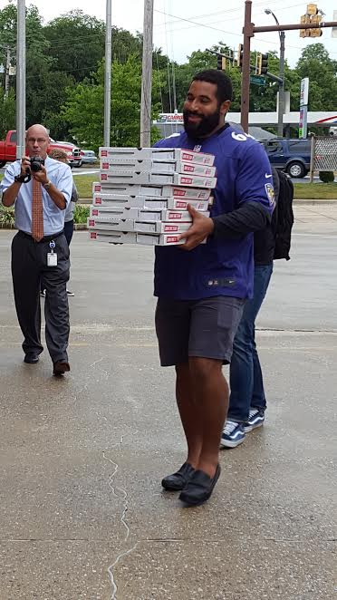 John Urschel carries a stack of pizzas while reporters take photos.