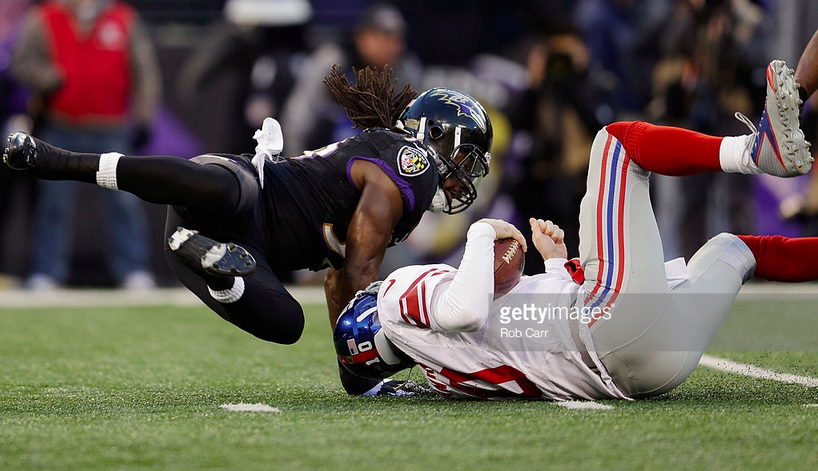A Ravens player takes down Eli Manning of the Giants.