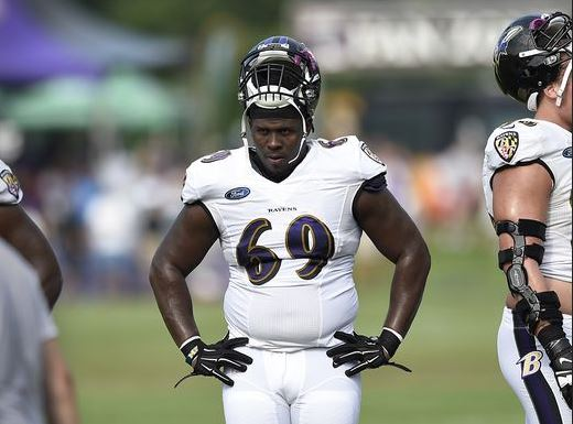 Willie Henry of the Ravens stands with his hands on his hips and helmet up over his face.