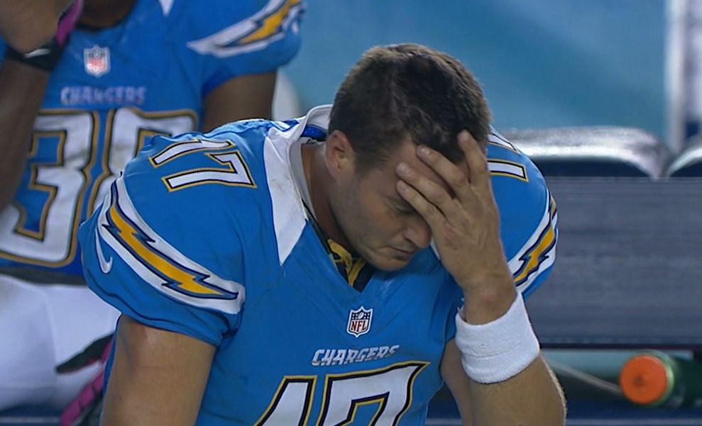 Philip Rivers sits with his head in his hand on the sideline.