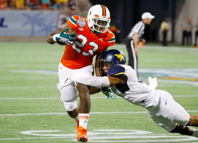TE Chris Herndon of Miami runs with the ball as a WV defender tries to tackle him.