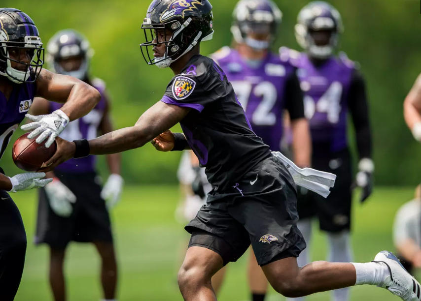 Lamar Jackson hands the ball off at OTAs