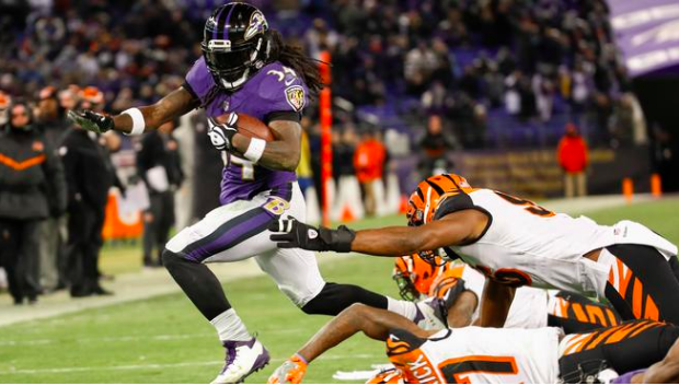Alex Collins carries the ball past Bengals defenders.