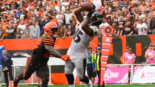 Michael Crabtree lunges for a pass as a Browns defender grabs him.