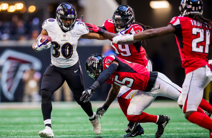 Kenneth Dixon runs as Falcons defenders chase.