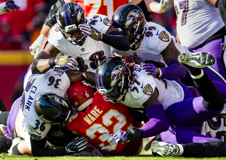 Ravens players pile on KC's RB Ware.